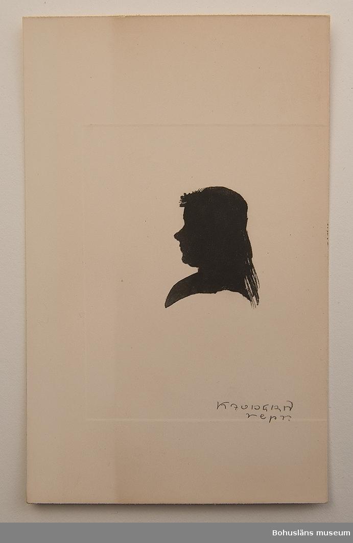 Reproduktion i djuptryck av silhuett klippt i svart papper. bröstbild vänd åt vänster. Kvinna med halvlångt hår fästat i nacken och i pannan nåon slags dekorativ hårprydnad eller lättare huvudbonad. Signerad KAUDERN repr.