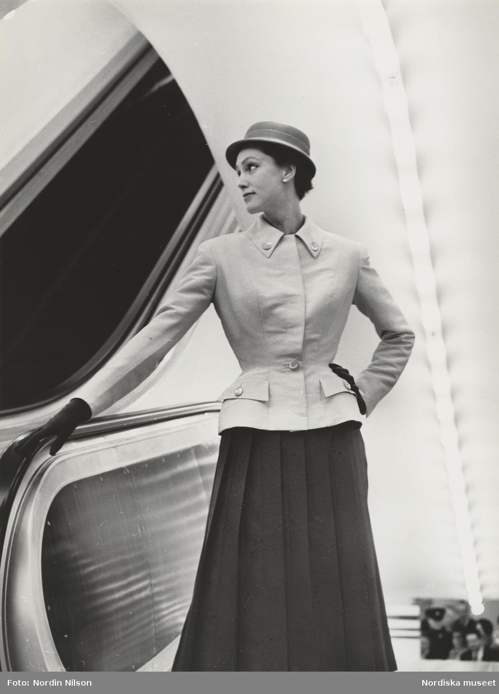 Modell i ljus jacka, veckad kjol, hatt och handskar vid rulltrappa. Original Patou.
