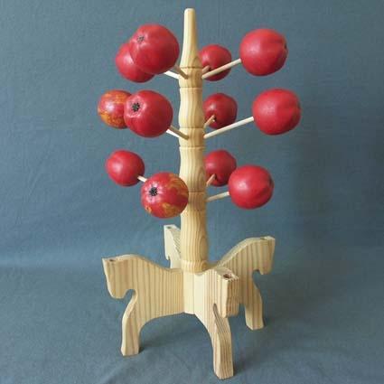 Ljusstake bestående av femton röda äpplen, tolv pinnar att fästa äpplen på, en mittpinne och en fot bestående av fyra hästformade delar.