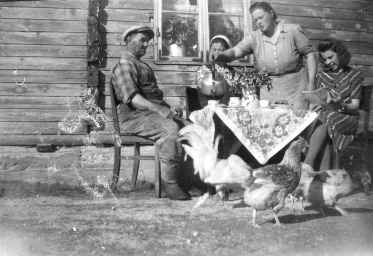 Tre kvinner og en mann utenfor et hus i Nyhamn. På bildet serverer Hildur Davidsen kaffe til gjestene Johan og Helga Johansen og damen til høyre er Haldis Basso (f. Biedilæ). Hildur og Karl Davidsen var nærmeste nabo til Idor Niska. Bildet er tatt ca 1945-1950. Rundt kaffebordet svinser høner og en hane.
