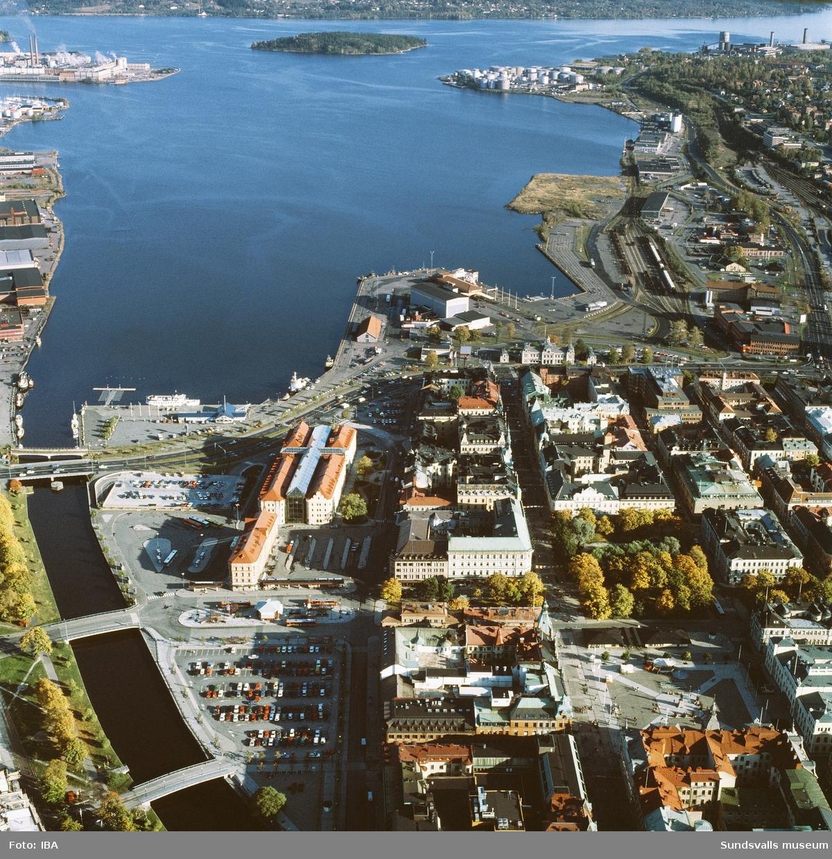 Flygbild över centrala Sundsvall med Selångersån till vänster, hamnen och södra kajen till höger i bild. Det nybyggda Kulturmagasinet med glasat tak ses i mitten av bilden.