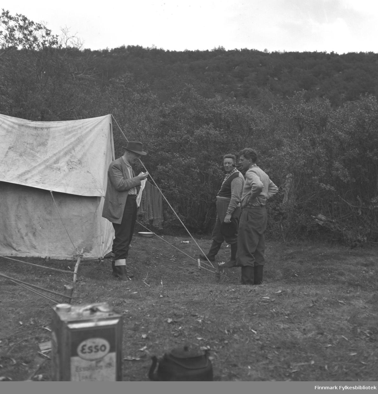 Tre menn fotografert utenfor et telt. Nærmest teltet står Fridtjof Jacobsen. Stedet er ukjent.