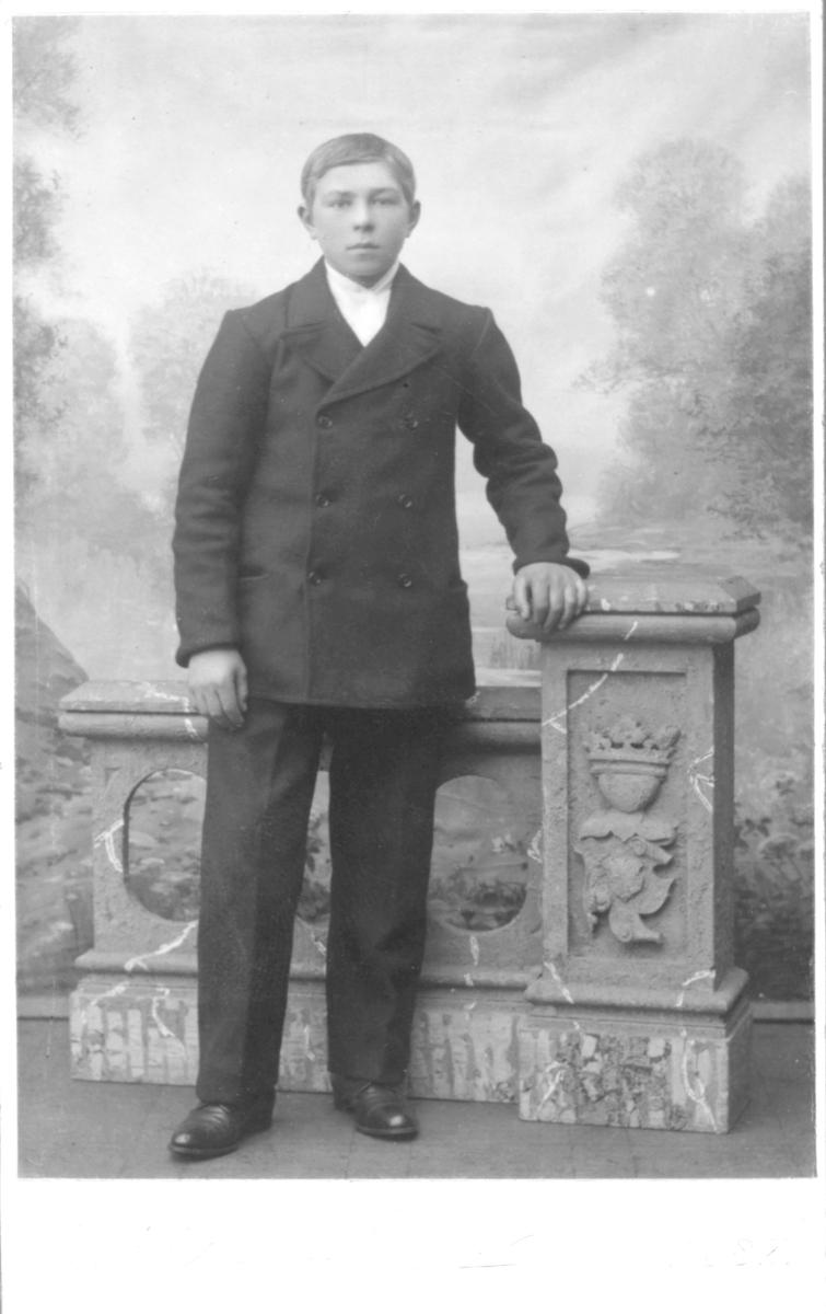 """Portrett fra en ung gutt, Hilmar Isaksen. Han er kledd i dobbeltspent dress og poserer foran en håndmalt landskapsbakgrunn, med en hånd på en murt søylevegg/kulisse. I Digitalarkivet er Hilmar Edvin Isaksen registrert under folketelling i 1910, født 01.04.1891 i Lebesby, Kjøllefjord. Han er registrert som fisker med oppholdsted """"Lofoden"""". Adresse er """"Finnegaden 386."""" og han er oppskrevet som """"stedsøn"""" til Arnt Verriö og Brita Marie Verriö, født Ranta. De har selv 4 sønner og 2 døtre. Om Arnt Verriö står det at han """"gik vægter i byen"""" og var dessuten notert med yrke: Fiskeri, kreaturhold"""".   Trond Ballo har kommentert bildet: """"Hilmars mor var Britha Marie (f. Ranta) Wærriø. Britha Maries sønn Hilmar har ingen far nevnt ved dåpen. Hilmar kom til Vadsø da han var ett år gammel, og begynte som fisker i 13-14 års alderen. Men han begynte som sesongarbeider i 1907-08 på AS Sydvaranger i Kirkenes. Mens han bodde i Vadsø kom han med i arbeiderbevegelsen som ble stiftet i Vadsø i 1908. Da han flyttet til Vardø i 1915 ble han formann i partiforeningen der, siden også i Vardøfiskernes Agnforsyning. I 1923 begynte han som betjent på Vardø Samvirkelag, senere 1.betjent og flyttet da kort tid etter til Kirkenes der han gikk over i samme stilling i Kirkenes Samvirkelag. I 1927-28 ble han bestyrer på Samvirkelaget på Skogfoss, men flyttet derfra til Jakobsnes der han ble boende med sin familie. Han var også hovedstyremedlem for Finnmark i Handel og Kontor, formann i avdeling på Kirkenes og medlem i 30 år. I begynnelsen av 30 årene ble han valgt inn i herredstyret, medlem av formannskapet i to perioder, og etterhvert en rekke tillitsverv i kommunen. Fra 1923 til 1941 var han medlem av forliksrådet. Etter frigjøringen var en formann i rådet. I samme periode var han medlem av herredstyret og formannskapet, og i siste periode var han viseordfører. Da ordføreren ble sendt på tinget overtok Hilmar ordførerklubben."""" Han var også formann for fylkesforsyningsnemda, representant for Sør-Vara"""