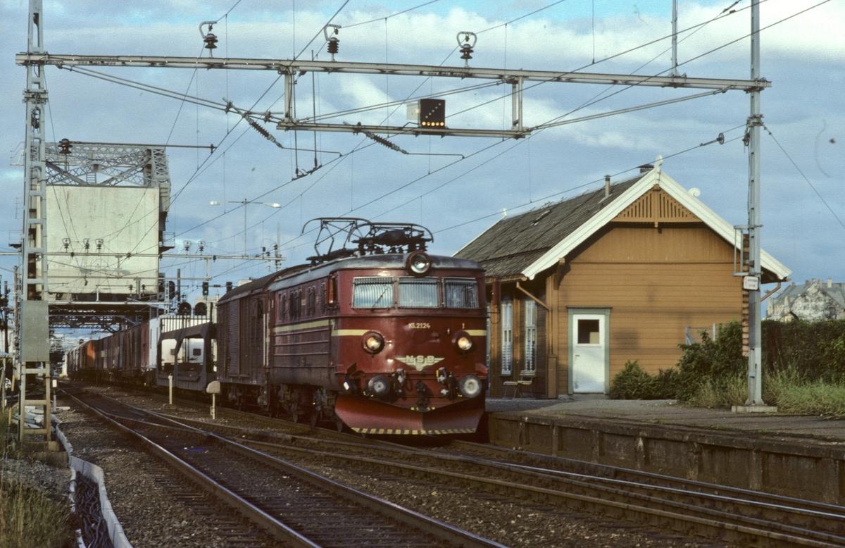 NSBs godstog 5712 med elektrisk lokomotiv El 13 2124 kjører ut fra Trondheim over Skansen bru, og forbi Skansen holdeplass.
