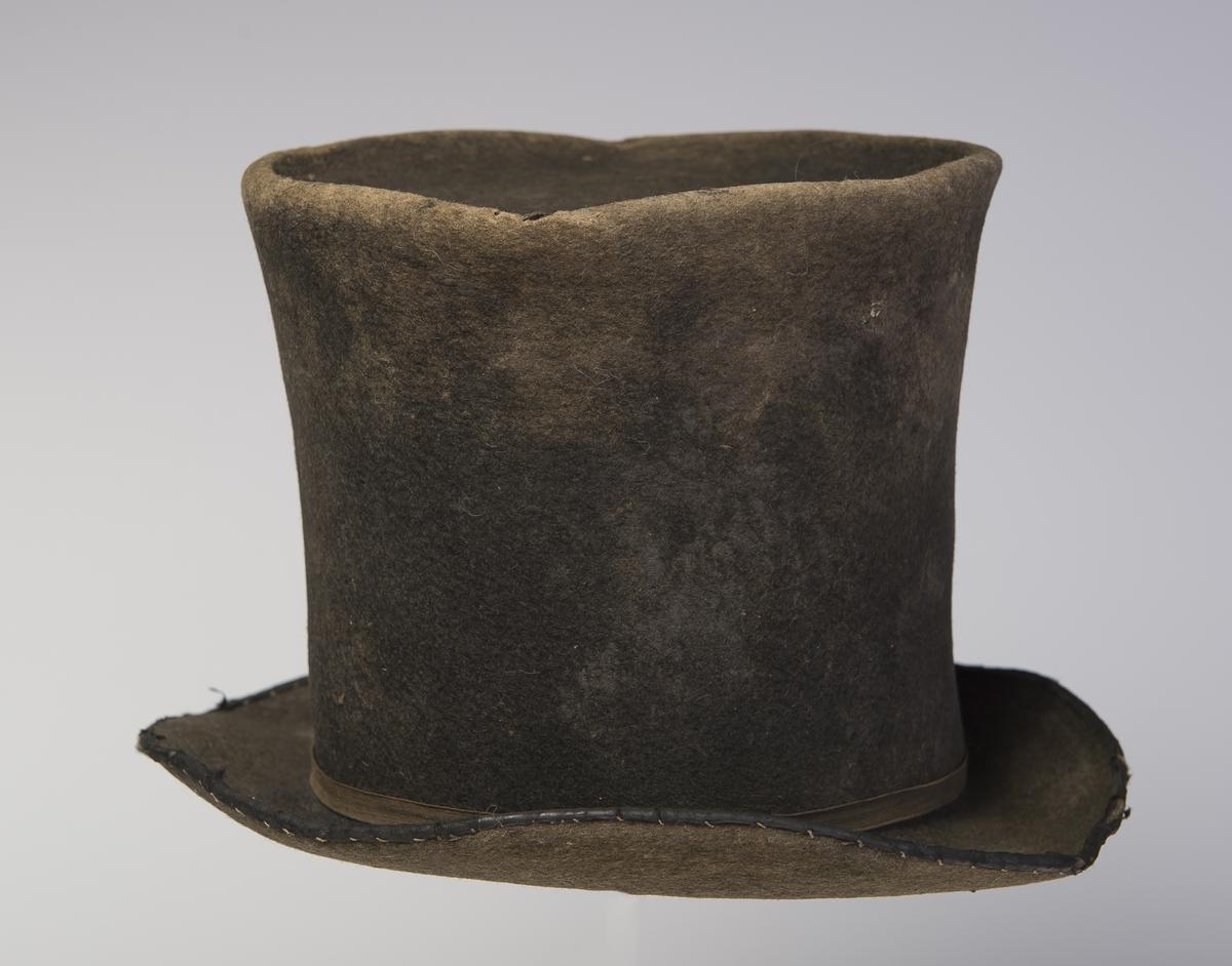 Filthatt med høy stiv pull som er flat på toppen. Bremmen har påsydd et skinnstykke på undersiden av bremmen. Rundt ytterkanten av bremmen er det påsydd et smalt bånd. Inne i pullen er det et papir med trykk på. Svettebånd med håndskrevet tekst, noe uleselig. Halve høyden av hatten er foret. Rundt nedre del av pullen er det et smalt bånd med knyttet sløyfe på den ene siden. Øvre del av hatten har større omkrets enn lenger nede. Denne type hatt er forløperen til flosshatt.
