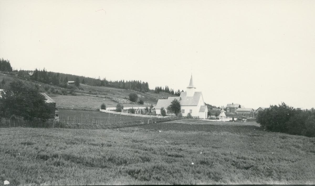 Røn kirke, skigard i framgrunnen og gårdsbebyggelse i bakgrunnen