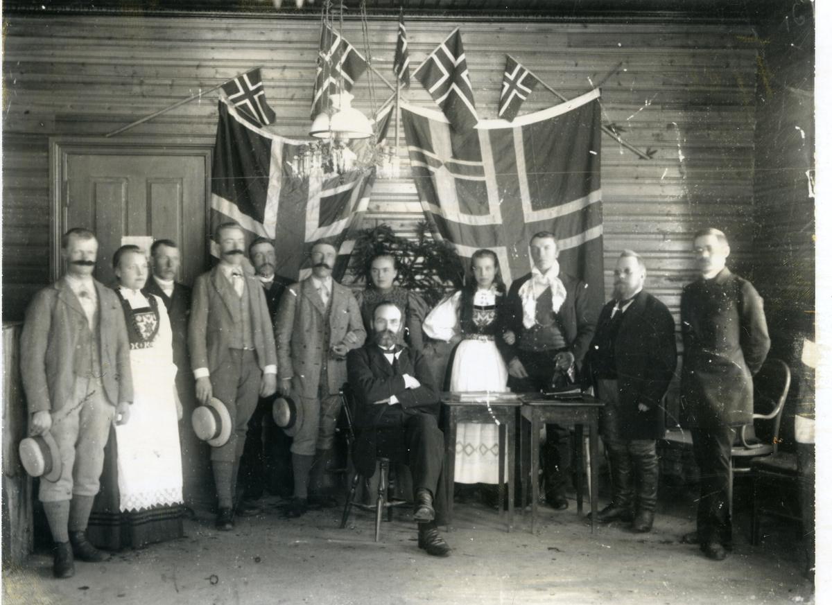 """Festkledde kvinner og menn, oppstilt foran tømmervegg. Veggen er pynta med norske flagg. To av kvinnene kledd i """"Nasjonalen"""""""