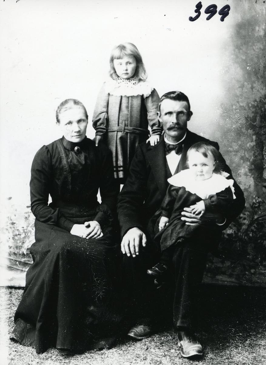 Portrett av kvinne og mann og to barn. Kvinnen er kledd i svart kjole, manne har mørk dress med sløyfe i halsen. Begge barna har hvite heklete krager.