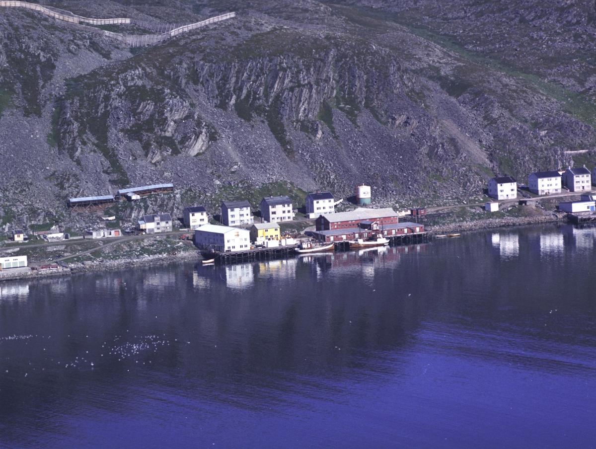 Flyfoto fra Kjøllefjord. Negativ nr. 122726. Fiskebruket midt i bildet var kjent som Aarsæther på 70-tallet, men var muligens FiNoTro tidligere? Helt til høyre på bildet sees enden av Dampskipskaia og til venstre enden av Kullkaia.