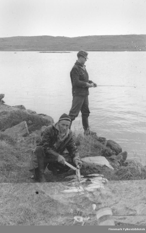 Fotografi fra Vadsø-traktene. Det totalt øde Peskvannet var et ønskested for fiskere. Fisken beit villig og turkompisene sløyde fisken etter hvert som den ble fanget. På dette bildet er Ernst Lebesby i gang med sløying, mens Edvard Irgens fortsatt fisker.