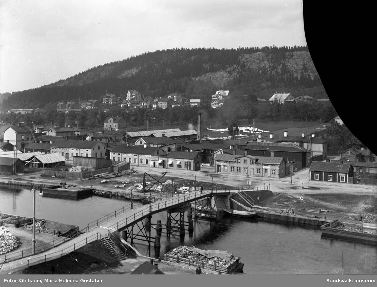 """Vy över Norrmalm. Gamla gångbron Puckelbron, även kallad """"Kamelryggen"""" över Selångersån (låg i Norrlandsgatans förlängning, raserades 1919 vid översvämningen). Den ersattes med en ny bro (som också kallades Puckelbron) i Malmskillnadsgatans förlängning. Glasplåten är skadad (en bit saknas i övre högra hörnet)."""