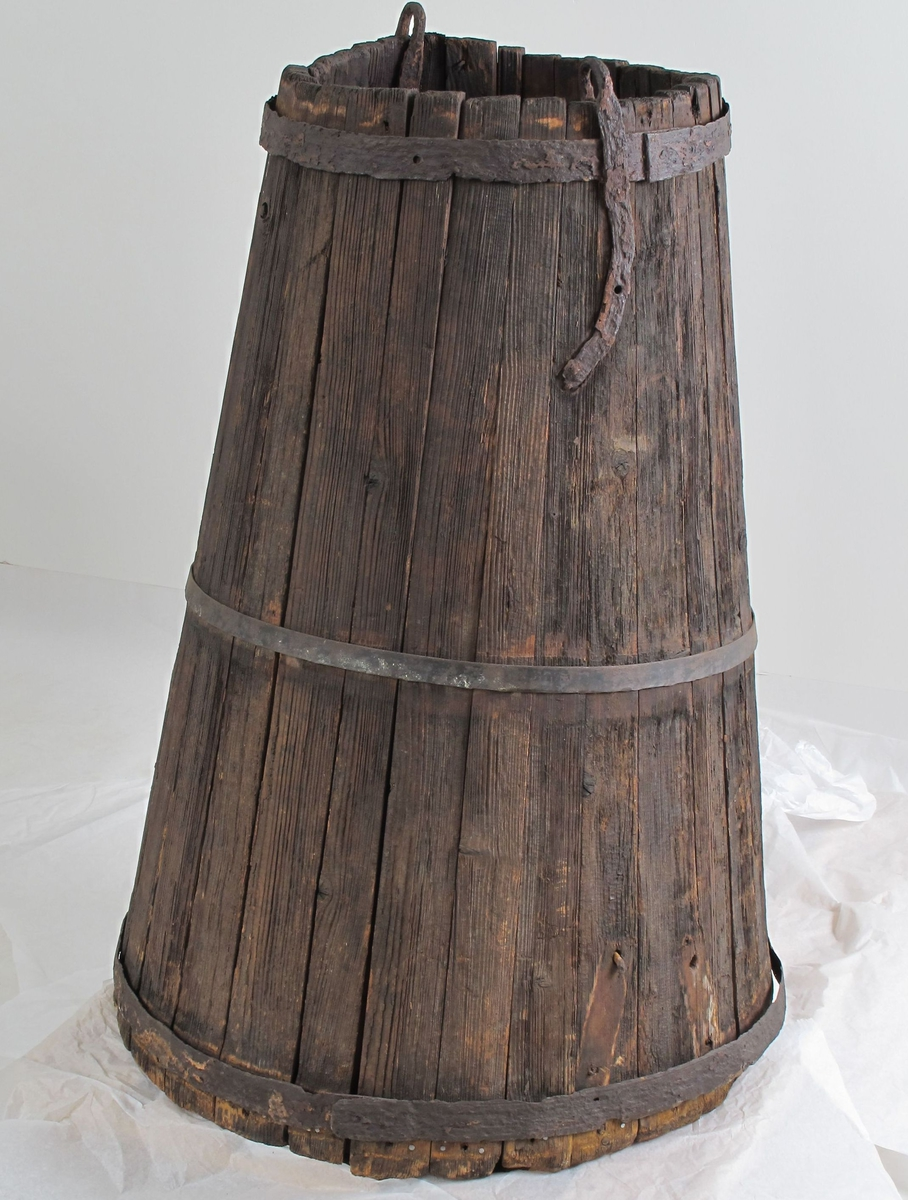 Vanntønne av tre (furu), gjorder av jern. Bøkkerarbeid. 2 stk  høye store   laggede kar, med innsnevret oppover. Laget av rettvokst furu. Stavene er tatt ut med årringene på tvers - stavene er smalnende oppover. To stk ørebeslag i overkant, til heising. Merker etter beslag i nedkant, til løfting i bunnen når tønnene skulle tømmes.   a) med en rød rusten gjord oppe og nede, merker litt nedenfor midten etter en til 2 hankeringer i  kanten.    b) en gjord oppe og nede,  mangler pm.   Tilstand: a)svært rød og rusten, b) svært fuktig, særlig i bunnen.