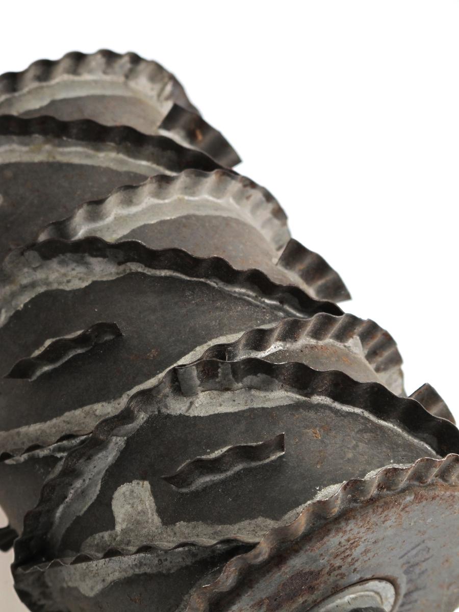 Kjevle  for utstikking av  sirupssnipper. Jernblikk.   Bred  sylinder  oppdelt i takkede ruter av oppstående   jernbånd. Kjevlet skyvbart om blikkrør.  Tilstand mai 1967: fortinningen avslitt, en del  rustangrepet.
