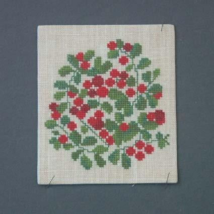 Liten bonad eller tavla med korsstygnsbroderi på linneväv uppspänt på kartong.