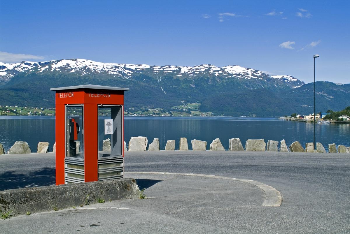 Telefonkiosken står i Nordstrandvegen 12, Sandane, og er en av de 100 vernede telefonkioskene i Norge. De røde telefonkioskene ble laget av hovedverkstedet til Telenor (Telegrafverket, Televerket). Målene er så å si uforandret.  Vi har dessverre ikke hatt kapasitet til å gjøre grundige mål av hver enkelt kiosk som er vernet.  Blant annet er vekten og høyden på døra endret fra tegningene til hovedverkstedet fra 1933. Målene fra 1933 var: Høyde 2500 mm + sokkel på ca 70 mm Grunnflate 1000x1000 mm. Vekt 850 kg. Mange av oss har minner knyttet til den lille røde bygningen. Historien om telefonkiosken er på mange måter historien om oss.  Derfor ble 100 av de røde telefonkioskene rundt om i landet vernet i 1997. Dette er en av dem.