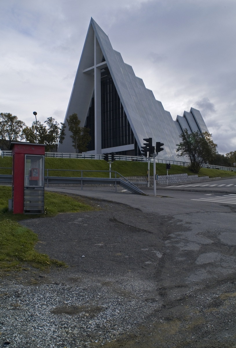 Denne telefonkiosken står ved Ishavskatedralen i Tromsø, og er en av de 100 vernede telefonkioskene i Norge. De røde telefonkioskene ble laget av hovedverkstedet til Telenor (Telegrafverket, Televerket). Målene er så å si uforandret.  Vi har dessverre ikke hatt kapasitet til å gjøre grundige mål av hver enkelt kiosk som er vernet.  Blant annet er vekten og høyden på døra endret fra tegningene til hovedverkstedet fra 1933. Målene fra 1933 var: Høyde 2500 mm + sokkel på ca 70 mm Grunnflate 1000x1000 mm. Vekt 850 kg. Mange av oss har minner knyttet til den lille røde bygningen. Historien om telefonkiosken er på mange måter historien om oss.  Derfor ble 100 av de røde telefonkioskene rundt om i landet vernet i 1997. Dette er en av dem.