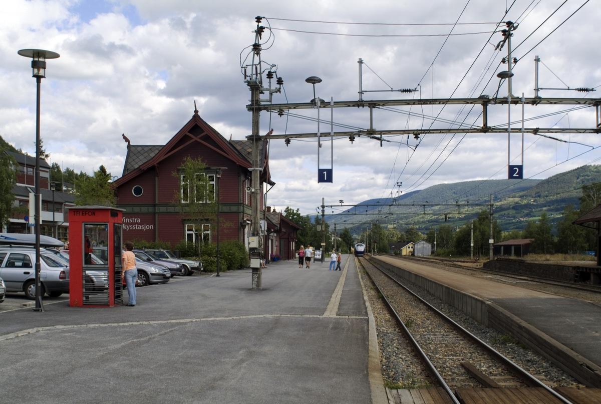 Telefonkiosken står på jernbanestasjonen på Vinstra, og er en av de 100 vernede telefonkioskene i Norge. De røde telefonkioskene ble laget av hovedverkstedet til Telenor (Telegrafverket, Televerket). Målene er så å si uforandret.  Vi har dessverre ikke hatt kapasitet til å gjøre grundige mål av hver enkelt kiosk som er vernet.  Blant annet er vekten og høyden på døra endret fra tegningene til hovedverkstedet fra 1933. Målene fra 1933 var: Høyde 2500 mm + sokkel på ca 70 mm Grunnflate 1000x1000 mm. Vekt 850 kg. Mange av oss har minner knyttet til den lille røde bygningen. Historien om telefonkiosken er på mange måter historien om oss.  Derfor ble 100 av de røde telefonkioskene rundt om i landet vernet i 1997. Dette er en av dem.