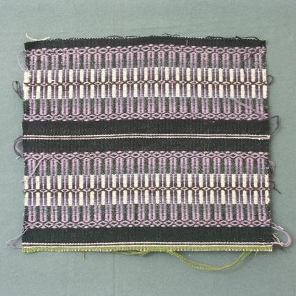 Prov, ev till löparväv, i rosengång med två lila bårder i rosengång, och svart och ljusgrå botten i inslagsrips.
