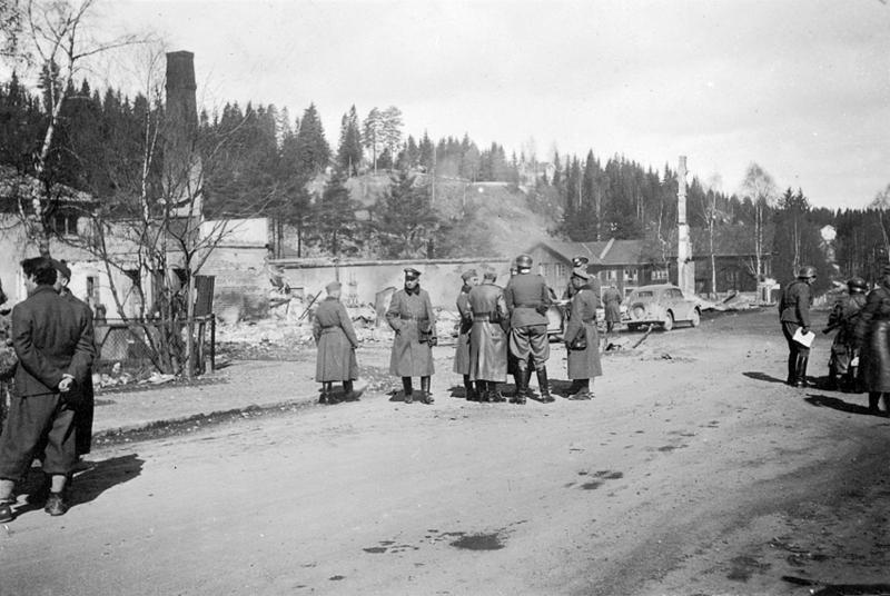 Rena sentrum var hardt ødelagt etter bombingen. Tyske avdelinger har inntatt Rena og sjef for angrepsaksen, oberst Fischer diskuterer med sine offiserer. Foto: Øyvind Leonsens billedsamling.