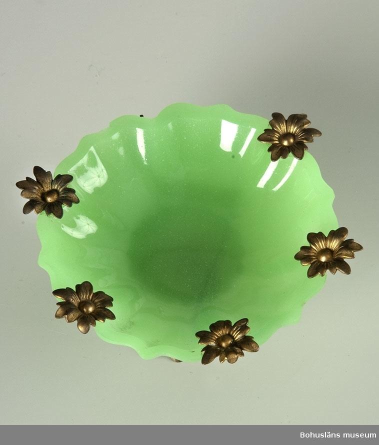 Pressad grön opalinskål på fotställning av pressad gulmetall. Dito material i sex metallblommor på skålens kant, varav en saknas. Kan möjligtvis ha använts till att lägga bl a ringar på, på ett damtoalettbord.  Ur handskrivna katalogen 1957-1958: Toalettartikel Grön glasskål med fot av gulmetall. Skålens diam.: 8,3. Föremålets H: c:a 4,3. Helt  Lappkatalog: 94
