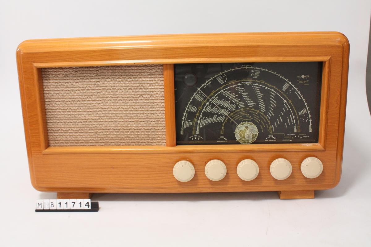 Form: Rektangulær. Avrundet sidekanter. Fronten på radioen er delt opp i to like deler, venstre felt er høytaler dekket med tekstil, høyre felt er skjerm for søkerinnstilling. Under søkerinnstillingen er fem skruknotter i hvit plast.