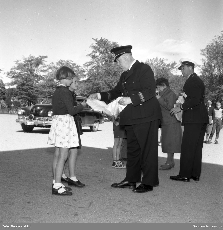 Ceremoni på GA-skolans skolgård där polisen delar ut priser/märken till barnen.