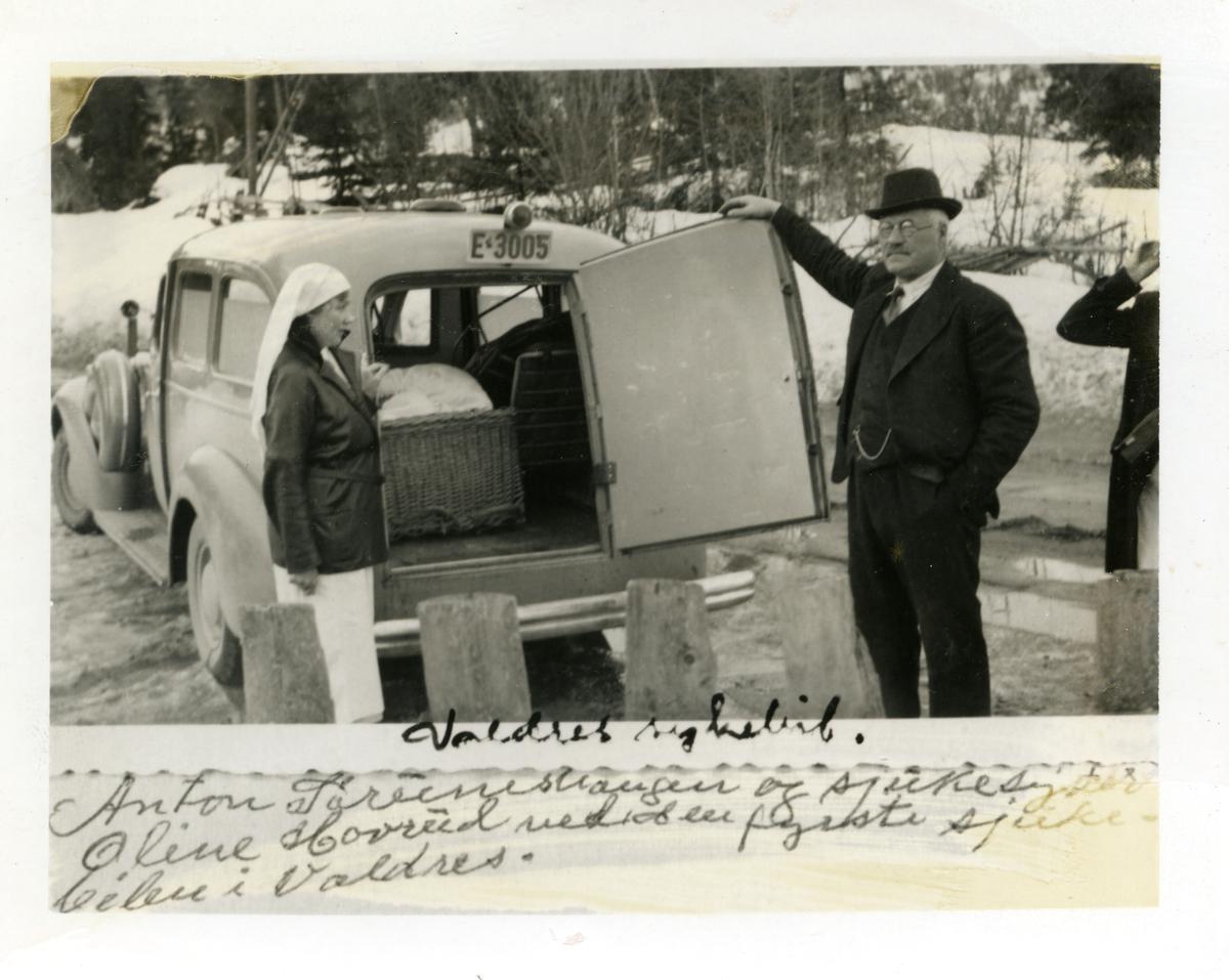 Den første sykebilden i Valdres. Sjåfør Anton Sørumshaugen og sykesøster Oline Hovrud står ved siden av bilen.