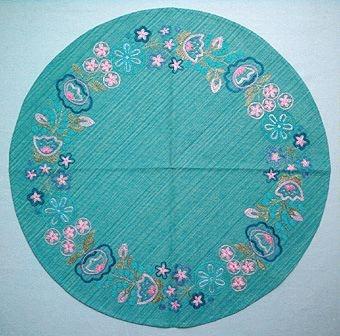 En rund och två fyrkantiga dukar LUSTGÅRDEN i halvlinne/lin och cottolin broderade med lingarn i kedje- och stjälkstygn en blombård i kransform runt om.  WLHF 499:1 - Rund duk. Blågrön-melerad linneväv, handvävd i lin/cottolin, med broderi i rosa, grönt, lila och blått. WLHF 499:2 - Fyrkantig duk. Mörkare blågrön linneväv med broderi i samma färger men något annorlunda nyanser.WLHF 499:3 - Fyrkantig duk. Blekt linneväv, vävd i kypert. Broderi i samma färger men något annorlunda nyanser. Mått 850x850 mm.