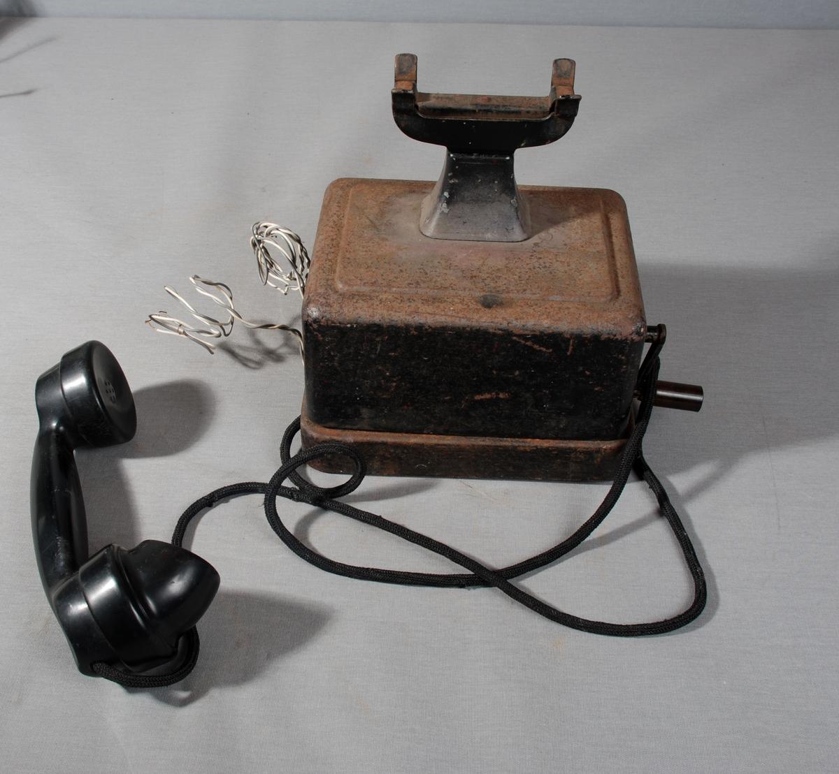 Telefonapparat med telelfonrør i gaffel på toppen av apparatet, sveiv på siden. Selve kassen står på sokkel av metall. 2 ledninger festet på siden av apparatet.