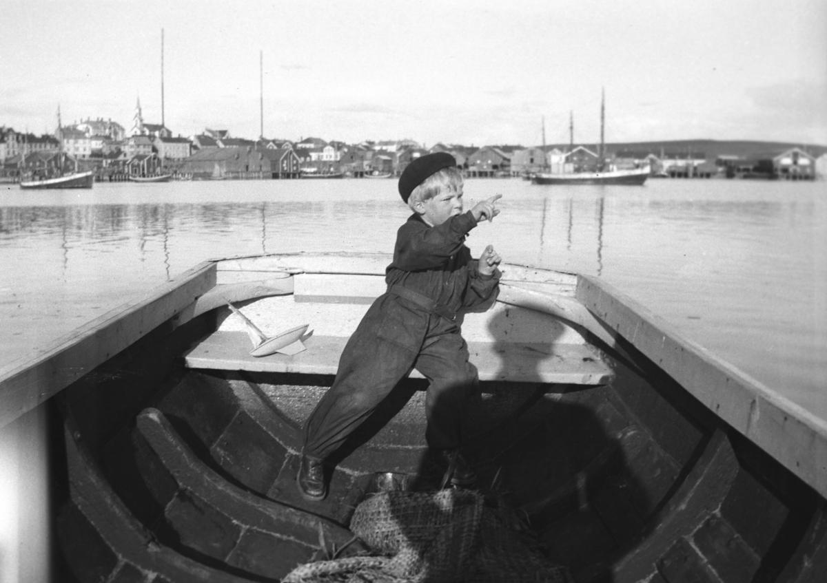 Tor Hauge sitter på hekken til en pram i Vadsø havn.