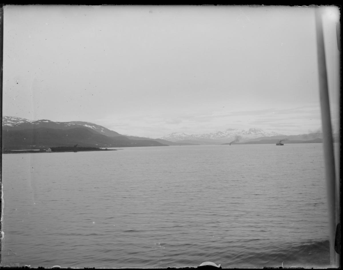 Kystlandskap med fjell. Bildet er tatt fra båt. Sjøboder i fjæra. To dampskip er på sjøen. Kanskje fra reisen nordover i 1912