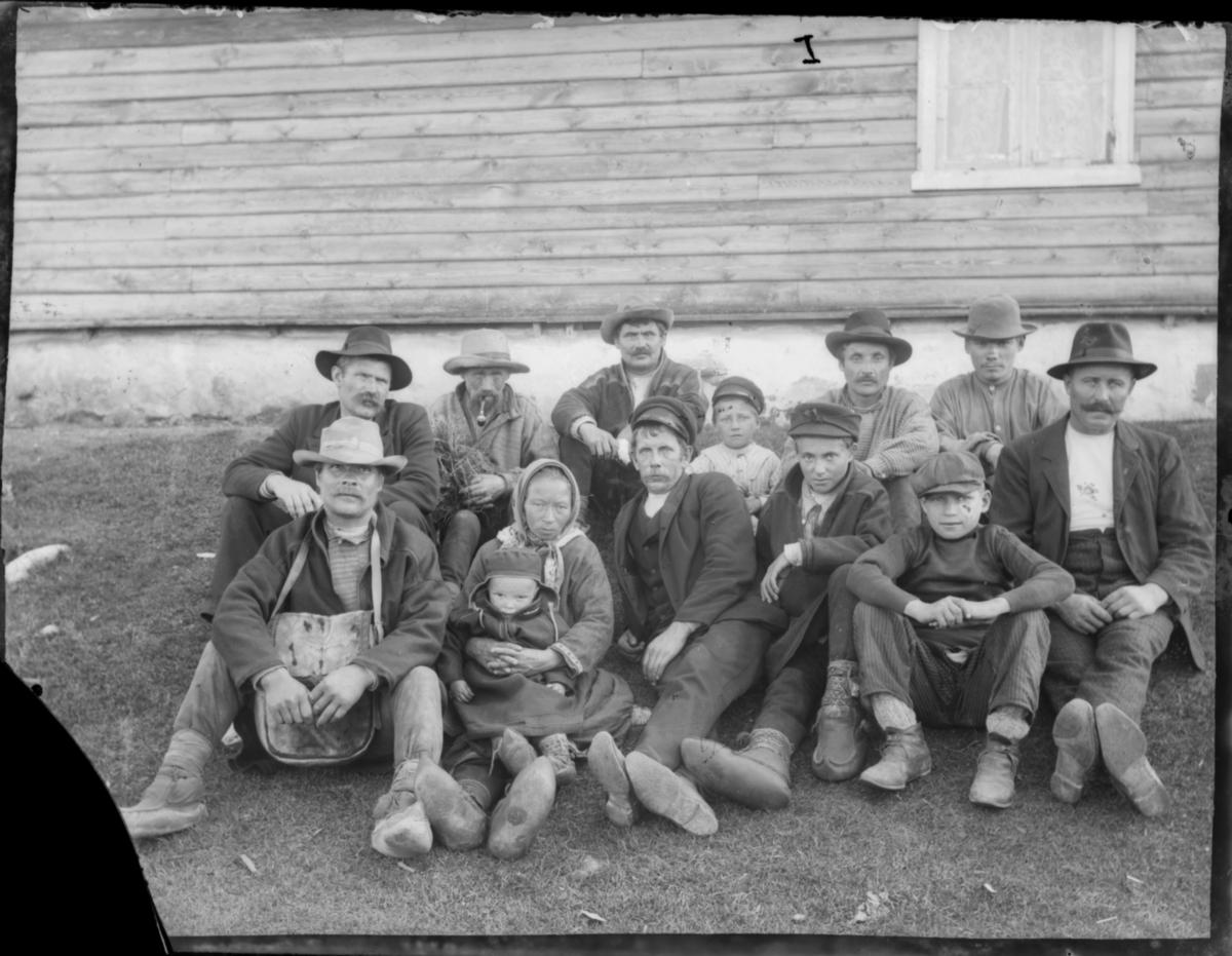 Åtte menn, en kvinne, tre gutter og ei lita jente som sitter på kvinnens fang. Kvinnen og jenta har samiske hverdagsklær. Mennene har hatter og vadmelsjakker, og en av dem har ei flott skinnveske. Samene har kommager med vevde bånd rundt anklene