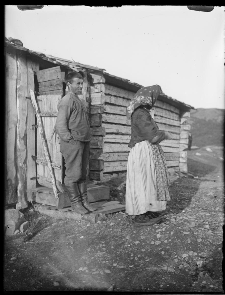 Skoltebyen Boris Gleb. En kvinne og en mann utenfor et hus i laftet tømmer Kvinnen i skjørt med forkle, bluse og skjørt. Mannen i støvler, bukse og skjorte