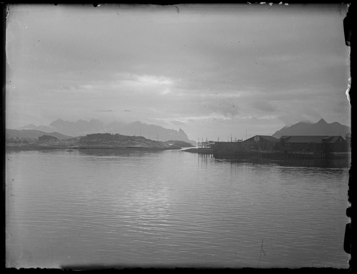 Bildet er tatt fra Hurtigruta og vi ser et fiskevær med kaier og pakkhus, omgitt av vakker natur