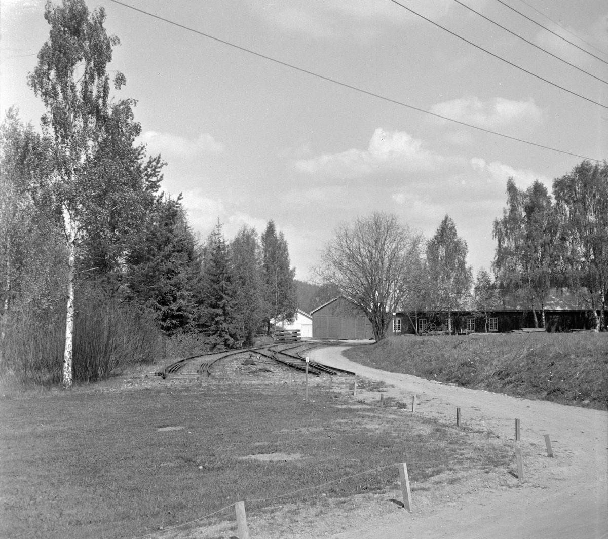 I bakgrunnen motorvognstallen på Solbergfoss stasjon på den nedlagte Solbergfossbanen. Sporene er delvis fjernet.