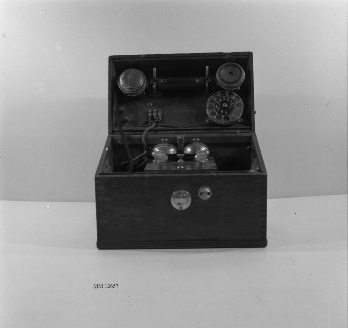 """Lådtelefon m/1908-1913. Se foto på MM 8254 (fingerskiva ej inmonterad). Inmonterad i låda av mahogny med snedskuret lock med handtag. På lockets översida rund förnicklad bricka märkt """"235"""" samt en kronstämpel. På lockets insida : """"11  58705""""."""