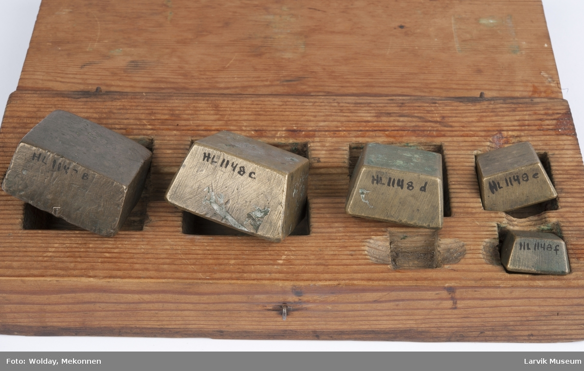 Form: rektangulær kasse med lokk/utskåret rom for 6  firkantede lodd/er utstyrt med 5 lodd