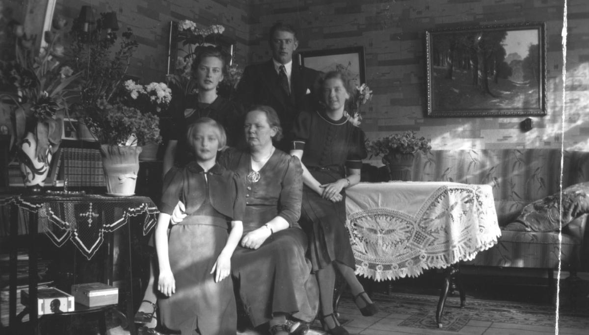 Menn, damer, en jente sitter oppstilt for fotografen i en stue. De har pyntet seg. Damene i mørke pene kjoler og herrene i dress. Det er store bilder på veggene. På hver side er det bord med store avskårne blomster.