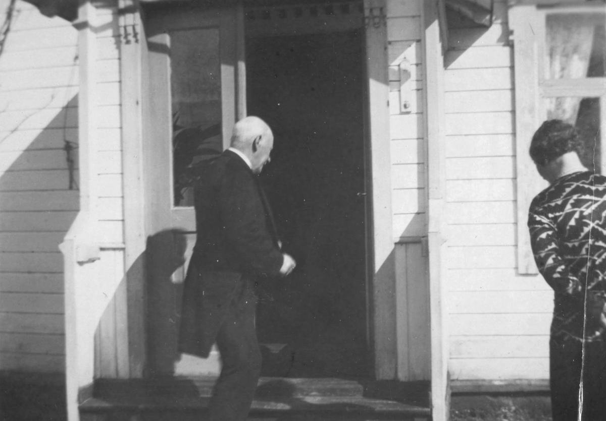 Karl O.Ohlsen på tur inn i huset. Til venstre ryggen av en dame.