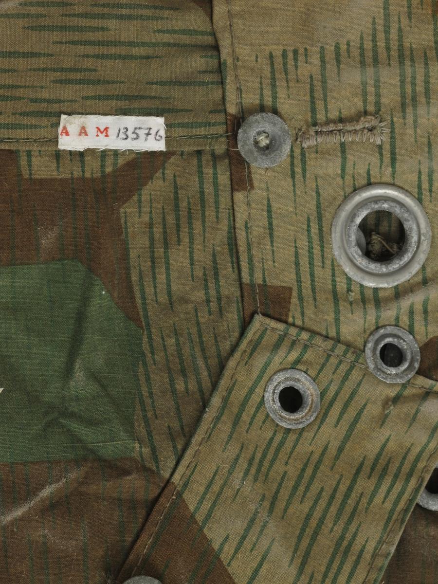 Teltduk, knappetelt, av kamuflasjestoff,  tysk, fra krigen 1940-45.   Seilduk, lysbrunt med grønne spetter,  grønne og brune uregelmessige flekker.     Stort trekantet stykke stoff, med knapper  og knapphull på alle sidene,  i midtsømmen en klaff, i hjørnene ring,  i den ene ring et tau.   Tilstand: en rift, ellers bra.