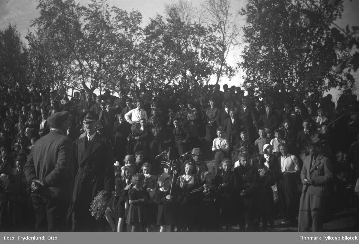 Kong Haakon VIIs besøk i Skipagurra 12. juli 1946. Her synger de frammøtte 'Ja vi elsker'. Kongen har fått blomster, og antakelig er mannen som står med ryggen til ordfører i Polmak kommune, herr Ballovara, som også holdt en tale for kongen