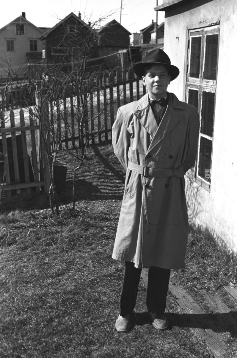 Konfirmanten Rolf Hauge i dress, frakk og hatt hjemme i Nyborgveien i Vadsø.