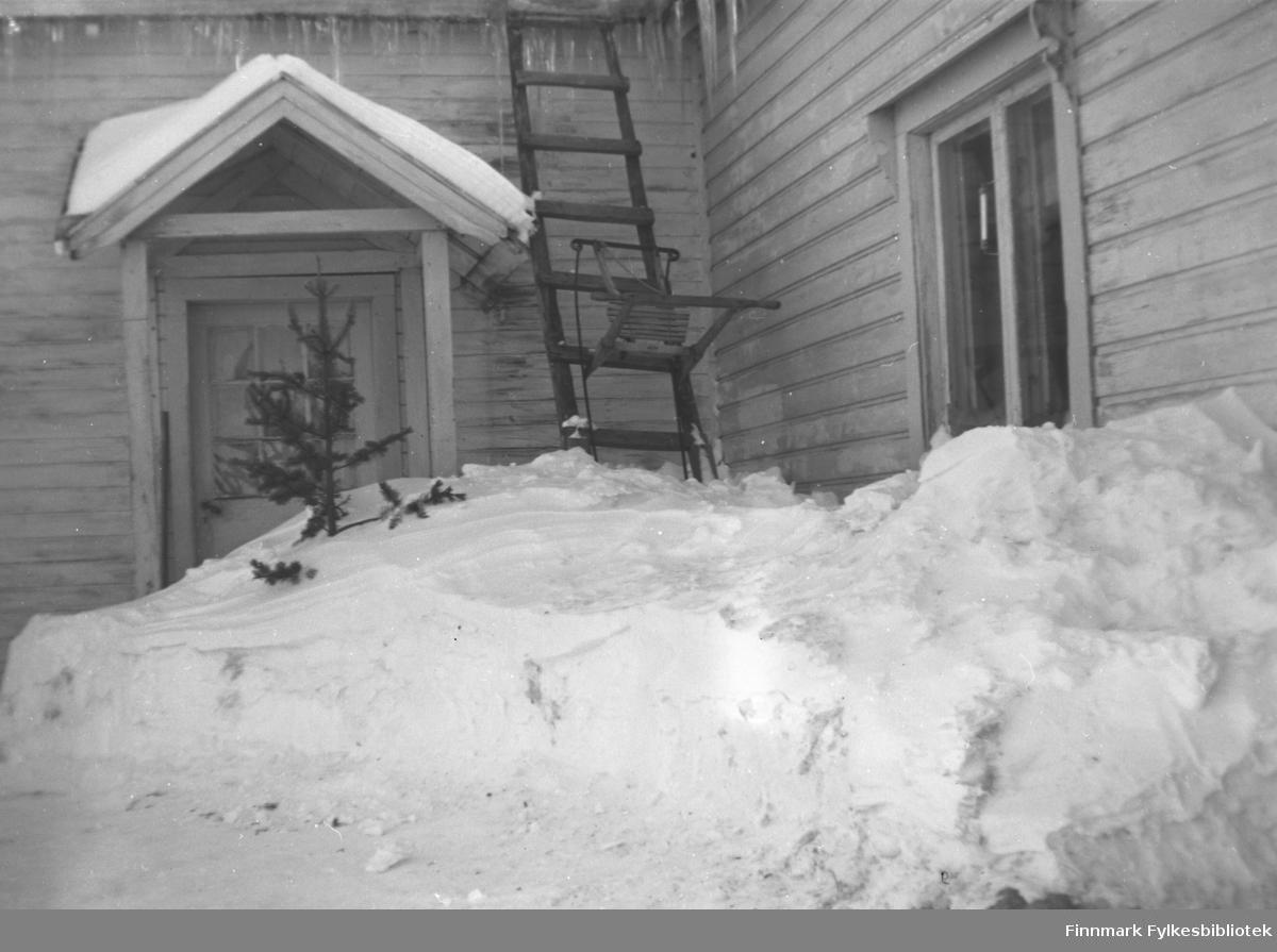 Vinterbilde fra inngangspartiet til våningshuset på gården Mikkelsnes i Neiden. En spark står stilt opp mot veggen, og et fordums juletre stikker opp av snøen
