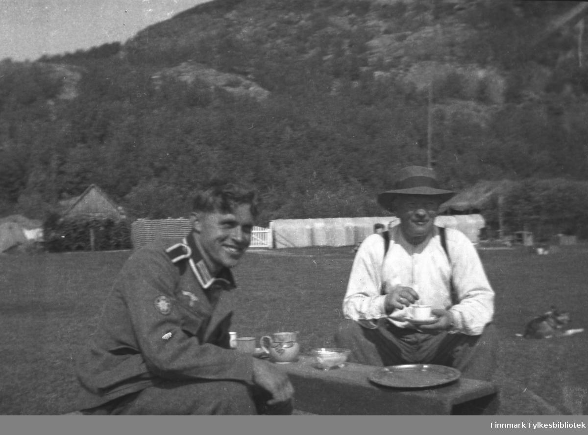 Østerrikeren Karl Brünzus i uniform og A.K. Mikkola drikker kaffe ute på Mikkelsnes. I bakgrunnen til venstre: Tyskernes brennevinsbrakke (for marinen), i bakgrunnen til høyre et telt til lagring av tyskernes ski. Skilageret ble bestyrt av Karl Brünzus