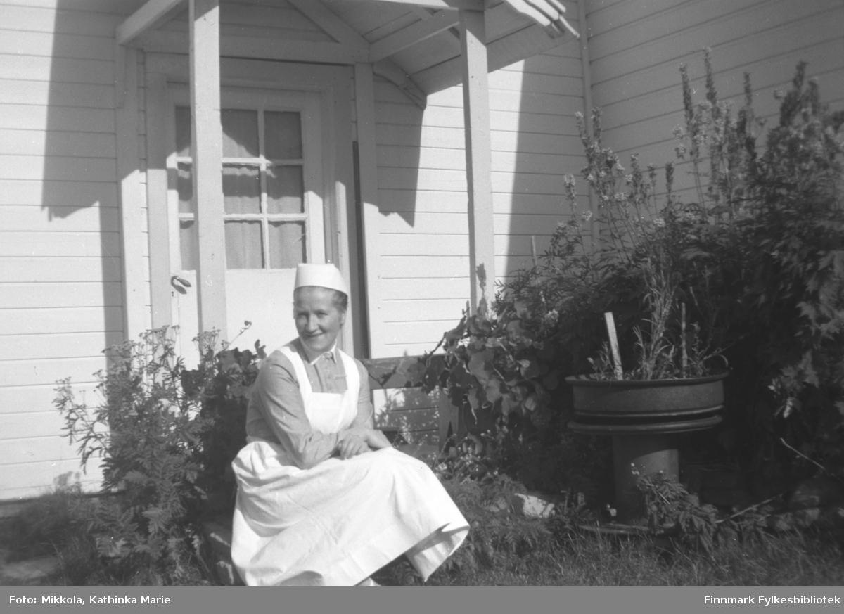 Herlaug Digre i sykepleieruniform ved inngangen til Mikkelsnes. Bildet er tatt ved samme anledning som 05007-236 og 05007-300