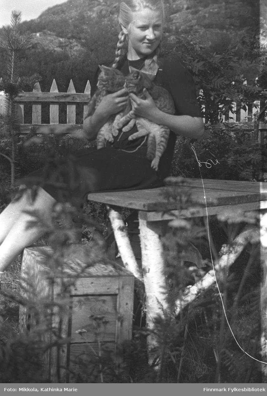 Herlaug Mikkola med to kattunger i hagen på Mikkelsnes