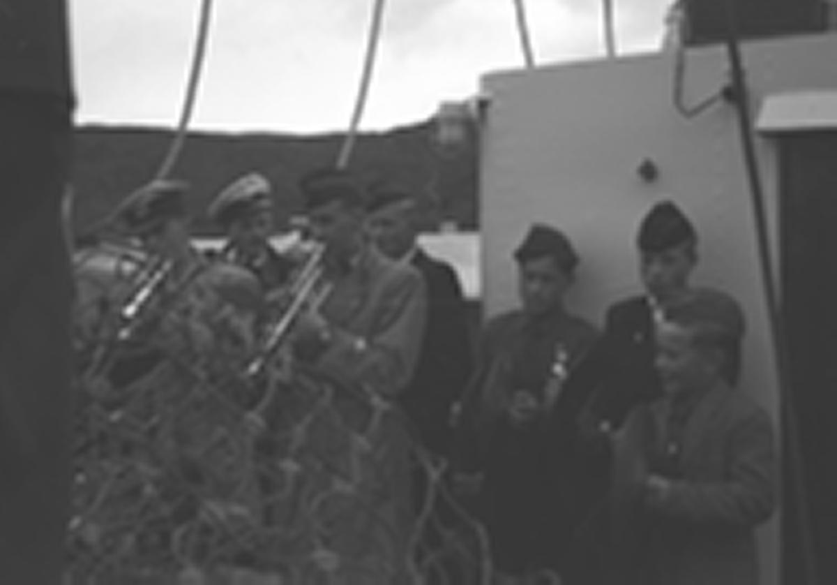 Noen personer, sannsynligvis fra et musikkorps spiller på dekket av en båt som kan være Hurtigruta. Personer og sted er ukjent, men minner sterkt om Hammerfest med Svartelva og hus på Hamran i bakgrunnen.