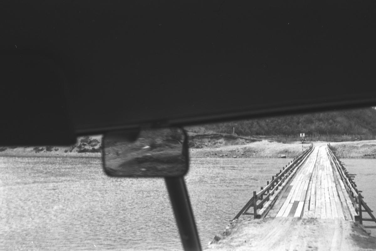 En lav trebro fotografert gjennom frontruta på et kjøretøy. Stedet er ukjent.