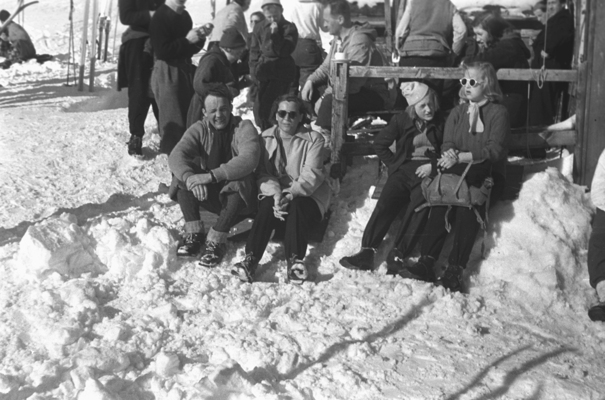 En værmessig flott vinterdag i Vadsø med endel folk ute på tur. Nederst til venstre på bildet sitter Anders Aune og ved siden av han sitter Frida Hauge. Resten er ukjente.