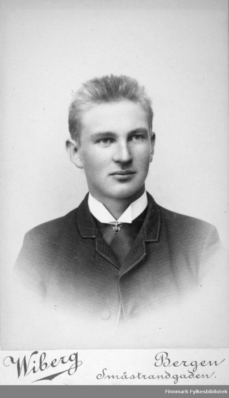 Portrett av en ung mann. Han har mørk jakke på seg og den hvite skjortekragen ses rundt halsen hans. Portrettet er tatt hos Halfdan Wiberg i Bergen.